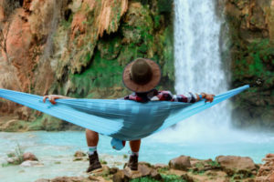 Human relaxing in a hammock in front of a waterfall